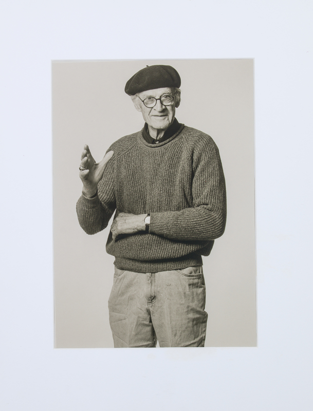 An elderly man with glasses and a beret. He has one arm crossed across his stomach and is gesticulating with the other hand.