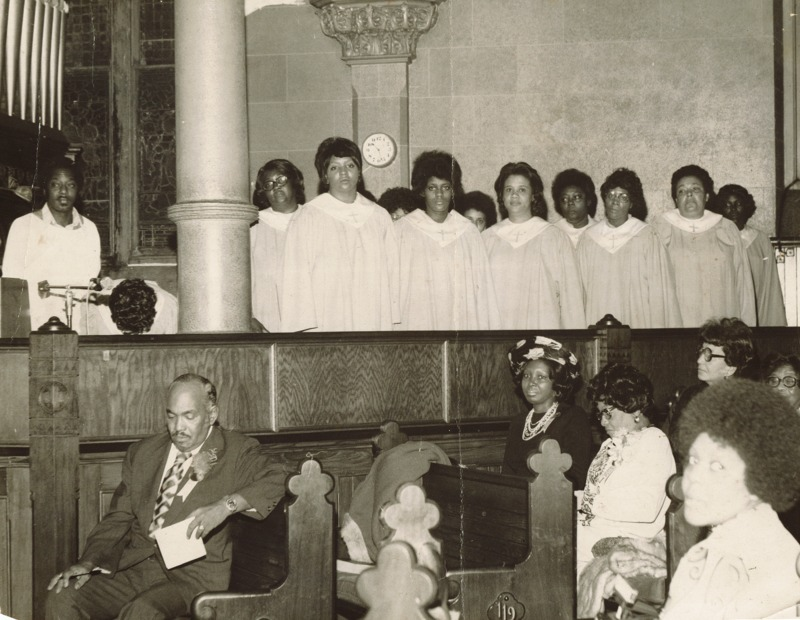 A group of female choir singers in white dresses and church visitors sitting on the benches.