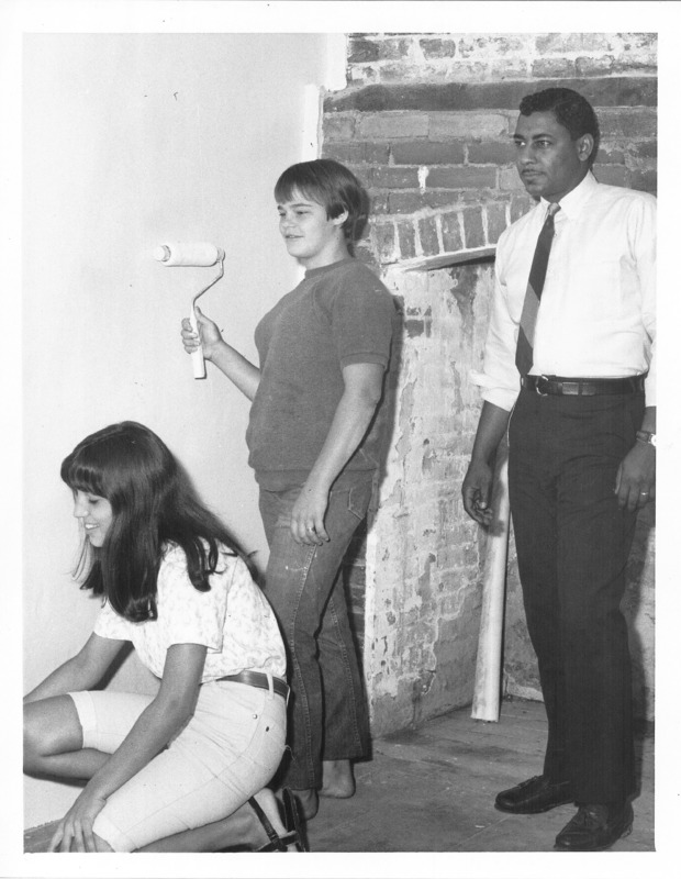 Two women standing in front of a wall with a roller and white paint and a man in a professional attire.