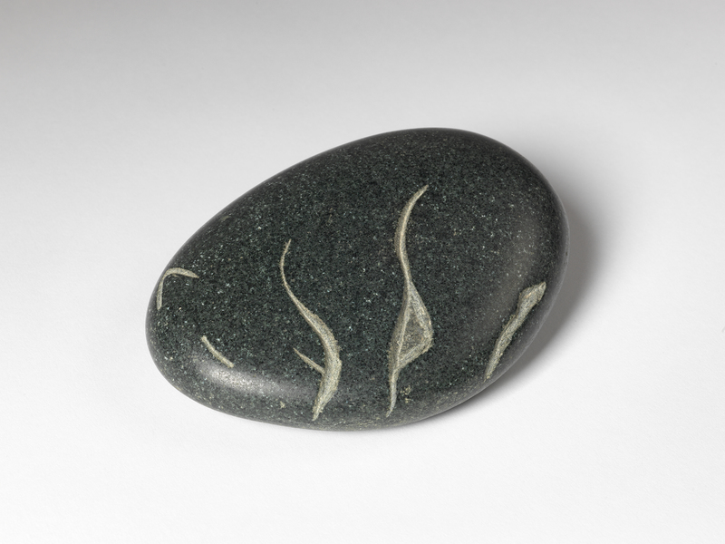 A smooth, speckled oblong stone with a simplistic sleeping bear carved into it.