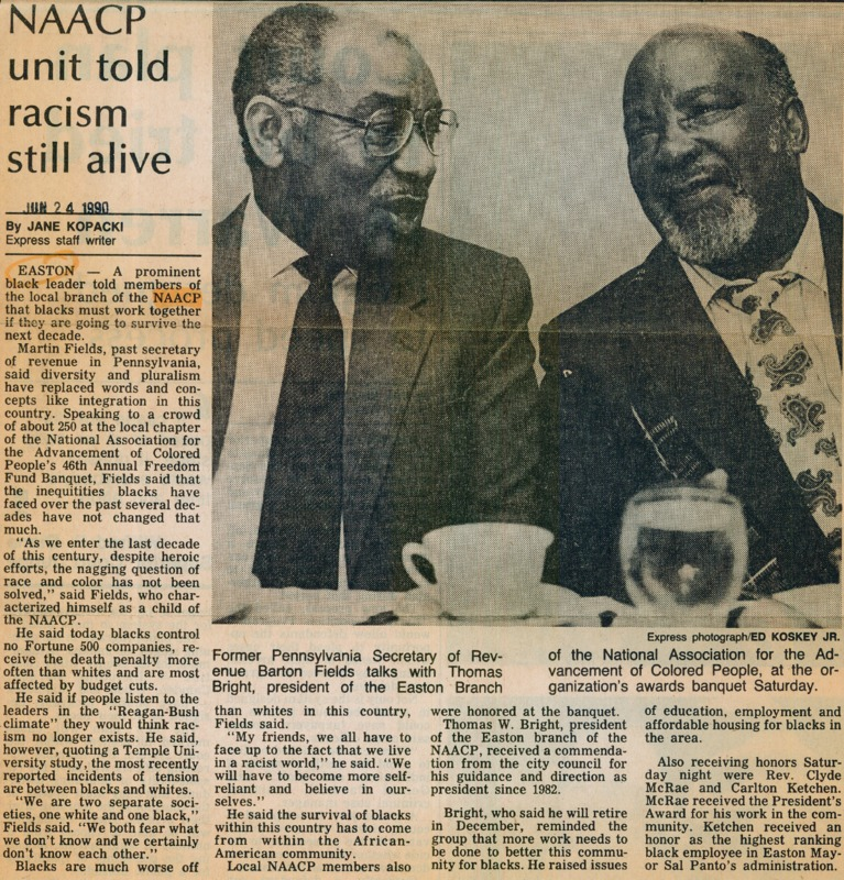 Newspaper clipping featuring two men in professional attires speaking to each other on a social event.