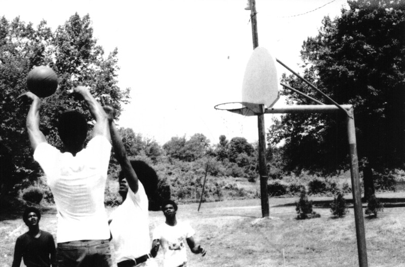 A group of men play basketball on the playground.