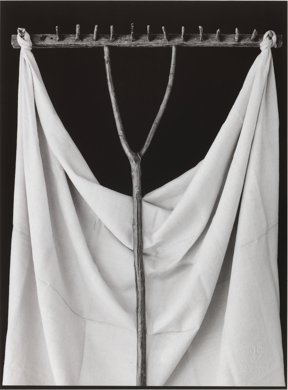 A wooden rake with a white sheet draped behind it. The ends of the sheet are knotted around the end prongs of the rake.