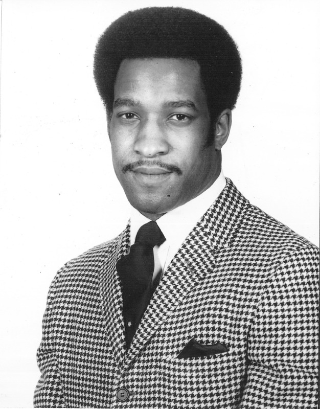 Formal headshot of a man in a houndstooth jacket