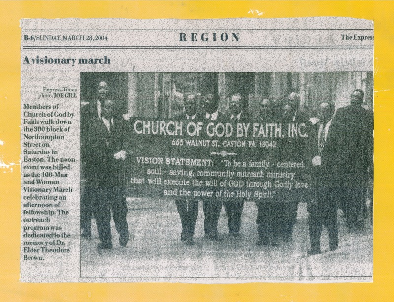 Newspaper clipping featuring a group of men in formal attires walking along the road and holding a poster.