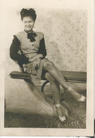 A woman in formal wear sitting on a bench. Her right leg is crossed over her left.