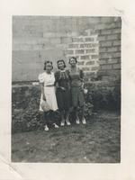 Three women in formal wear standing in front of a brick wall.