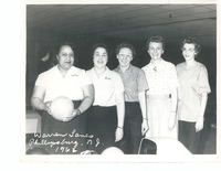Five women standing in a row. The leftmost individual is holding a ball.