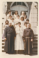 A large group of women in formal wear walking across a street.