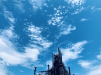 A steel mill against a blue sky. Its smoke stacks dominate the lower half of the image.