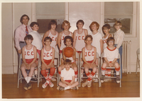 Two rows of boys. They are seated in the front row and standing in the back. Each is wearing a basketball uniform.