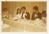 Multiple individuals dressed in formal wear sitting at a dining table. The presumed groom is making eye contact with the camera.