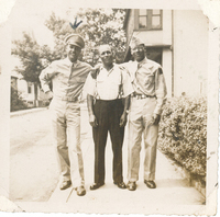 A man dressed in formal wear flanked by two servicemen in uniform with their arms wrapped around him. An arrow is drawn above the serviceman on the left.