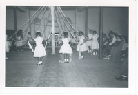 Young girls in white dresses dancing around a May Pole.