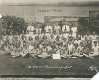 Several children sitting on grass in rows.