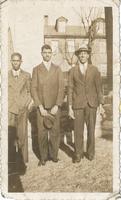 Three men in suits standing.