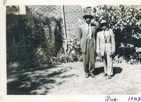 Two men in suits standing on a lawn in front of a house.