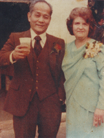 A man in a suit standing next to a woman in a light blue dress.