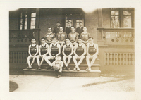 "Six young men wearing Easton basketball jerseys sitting on stairs. A small boy in front of them is holding a basketball with ""1928-29"" written on it."