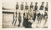 "Seven boys sitting atop a wall. Each of them is wearing a jersey labeled ""T7."" A man in a suit stands in front of them."
