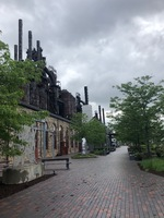 A park with brick paving. The steel mill can be seen to the left. Metal sculptures are scattered about the park.