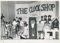 Multiple children observing two stage actors kissing. Each child is wearing a piece of paper with an illustration of a clock.