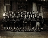 Football players standing in rows in front of a high school building