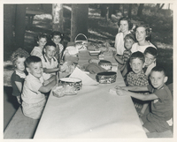 Children sitting at a dining table outdoors.