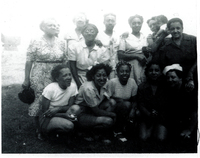 Several women gathered in two rows. The women in front are squatting while those behind them are standing.