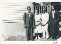 Two men in suits standing in front of the side of a house. They are flanking an older man and a woman.