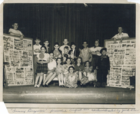 Several children flanked on either side by two individuals holding bulletin boards.