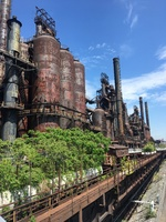 Rusted boilers against a partly cloudy sky. Trees have begun to overtake various areas of the plant.