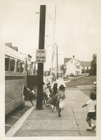 Several children boarding a bus.
