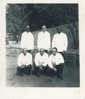 Three men squatting in front of three others that are standing. All six are in uniform.