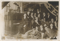 Several men sitting or standing. One is sitting at a piano.