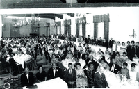 A large group of individuals gathered in a hall. All are dressed in evening wear. Candle chandeliers hang from the ceiling.