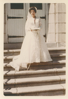A woman in a white dress standing on a flight of stairs.