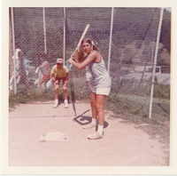 A young girl holding a bat to the right of home plate. A boy with his hands on his knees stands behind the plate.