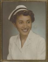 A smiling woman in a nurse uniform.
