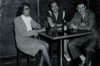 Two women and a man in formal wear sitting at a table.
