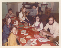 Several children seated at a table. There are various arts and crafts supplies on the table.