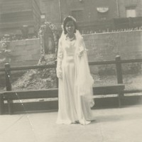A bride in her wedding gown in front of a Virgin Mary statue and a building