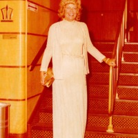 A smiling woman wearing holiday dress stands with a clutch in her hand at the stairs.