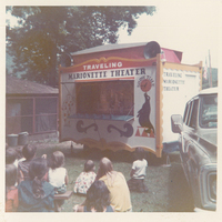 Several children watching a puppet show.