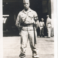 A man in a military police uniform. He is standing in front of a 710th Military Police Company sign.