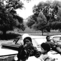A group of men sitting on cars and children sitting on the bench.