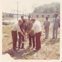 Four men holding a shovel. Other men are standing behind them and observing.