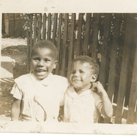 Two children standing in front of a wooden fence gate. Their arms are wrapped around each other.