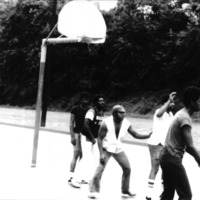 A group of men playing basketball on the playground.