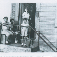 Three children at the top of a stoop. A woman is standing in the house's doorway.